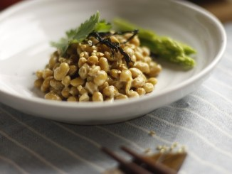 Natto in a white bowl with asparagus.
