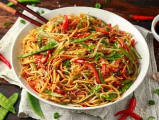 Chow mein, noodles and vegetables dish with wooden chopsticks.