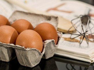 Eggs in a carton on a table next to a whisk.