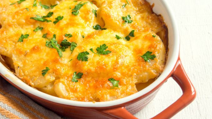 Potato gratin or potato dauphinoise with cream, cheese and parsley in baking dish