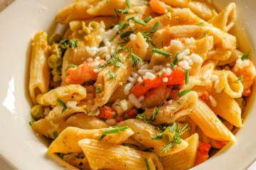 white bowl of rigatoni pasta, shrimps, chives, tomato sauce