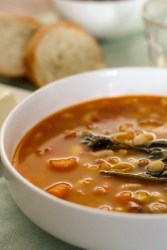 white beans in a tomate soup with fresh celery and chopped carrots. The soup is in a white round bowl with a few pieces of bread in the background.