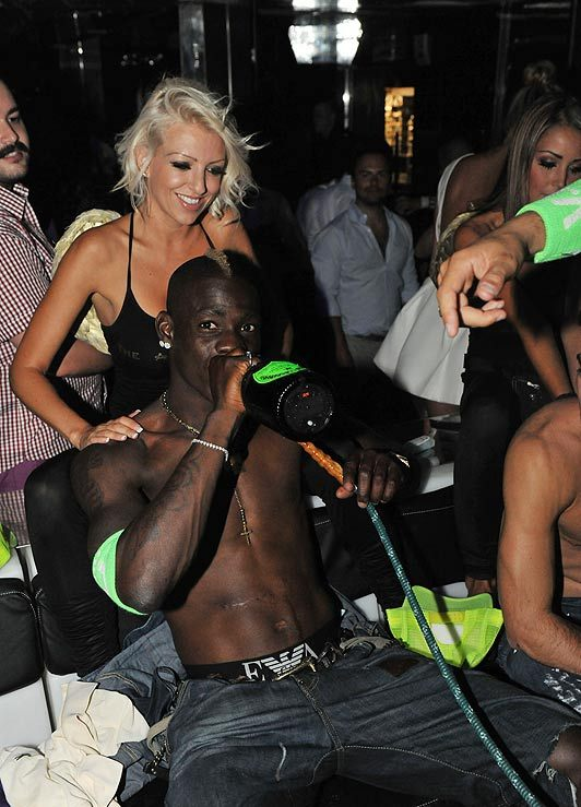 Mario Balotelli in a club in Saint-Tropez, drinking champagne and smoking in the VIP area