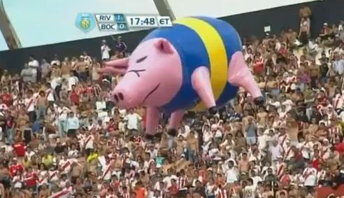 A giant inflatable pig wearing Boca Juniors colours, floated by River Plate fans during a derby game.