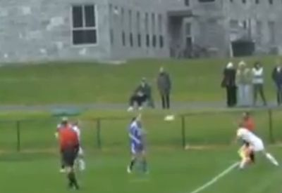 A women's football player takes a throw-in and throws the ball into an opposing player's face
