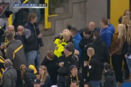 A Vitesse fan slips and drops beer while trying to kick ball