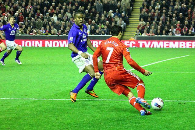 Luis Suarez takes on Sylvain Distin