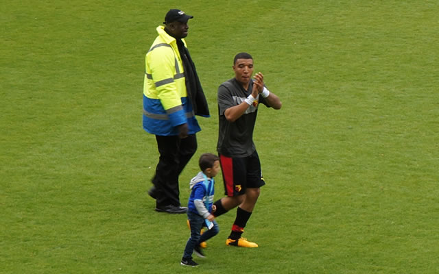 Troy Deeney and child celebrate with a lap of the pitch after the Watford v Leicester City play-off semi-final second leg