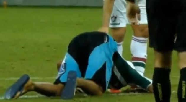 A Fluminense fan kisses Fred's feet during a pitch invasion