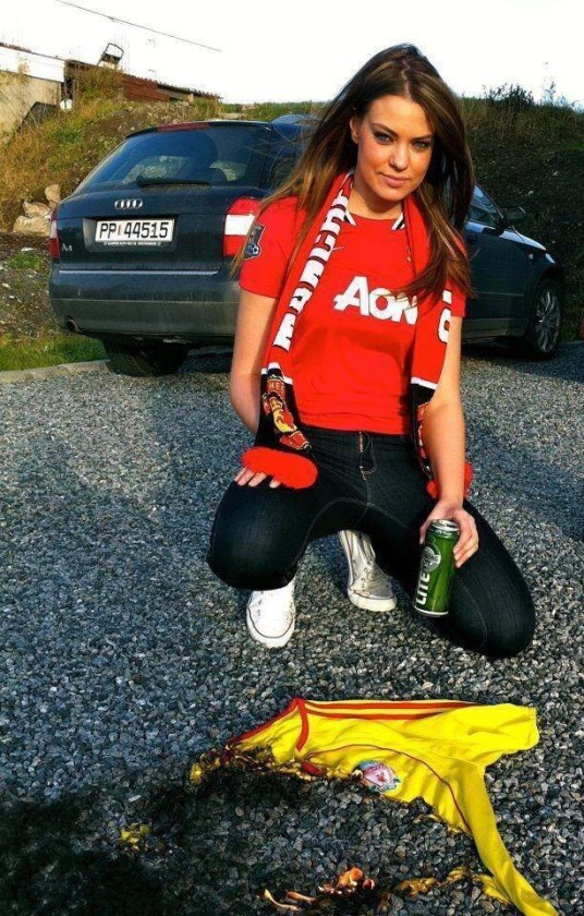 A hot female Manchester United fan burns Liverpool shirt