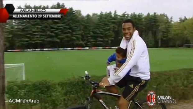 Robinho rides a bike wearing flip-flops and holding a child