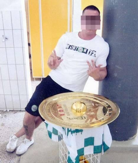 A Rapid Vienna ultra poses with Austrian Bundesliga shield