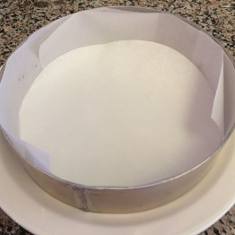 Put a cake ring on a large plate. Cut parchment paper into long strips and overlap them around the inner side of the cake ring. Place a round parchment paper at the bottom.