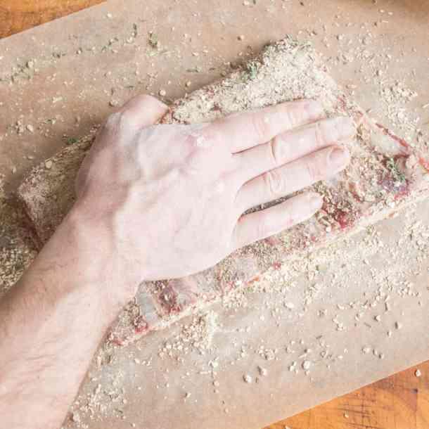 Rubbing a lamb rack with dried mushroom rub