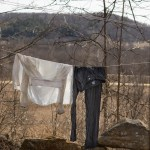 Drying permethrin-soaked clothes on a line outside.