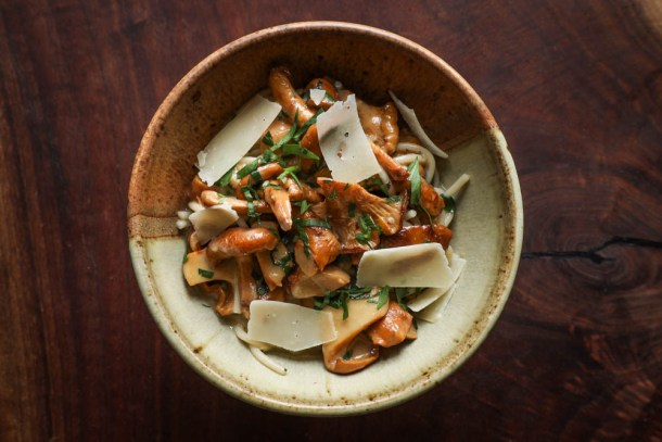 Chanterelle mushroom spaghetti with roasted garlic sauce and herbs in a ceramic bowl on black walnut background