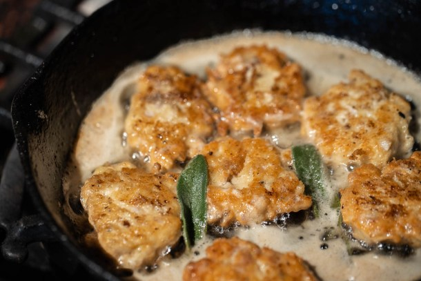 cooking brain fritters in a cast iron pan with sage leaves
