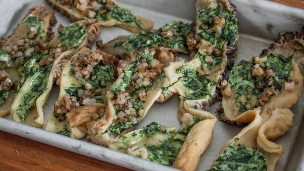 Spreading morels with garlic herb butter before baking