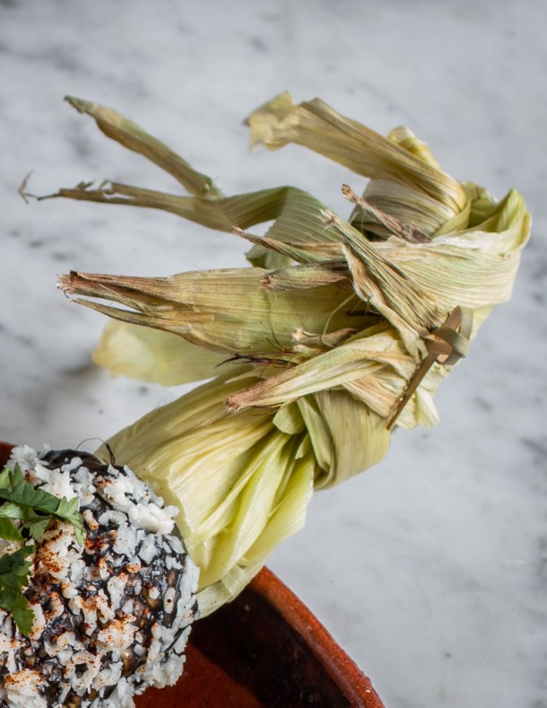 Tied husk of corn on an elote with huitlacoche puree