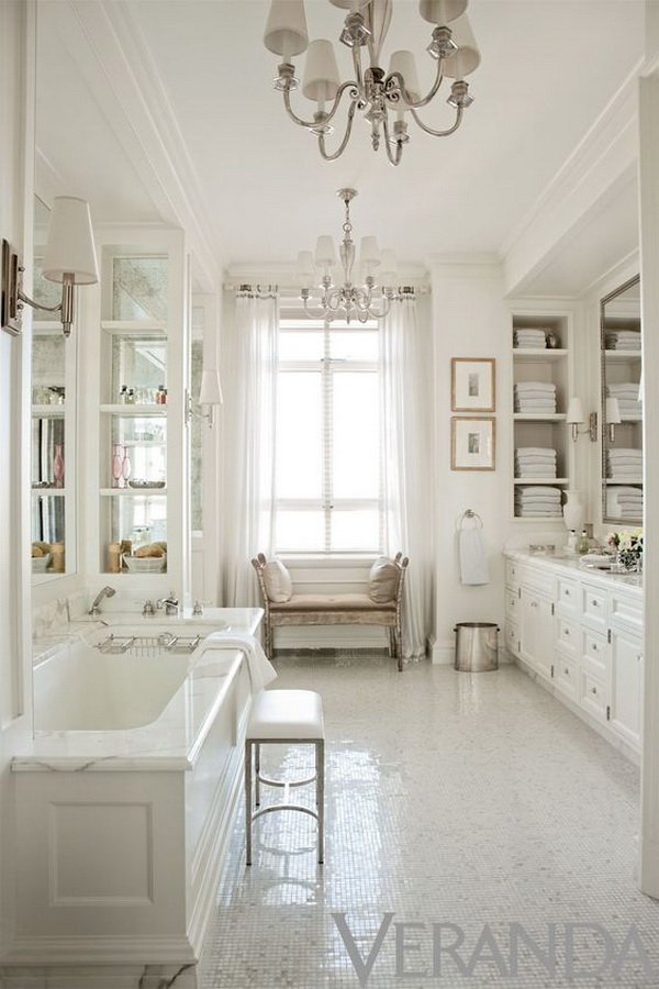 White-in-white bathroom with two elegant chandeliers and built-in wall shelves for bath towels storage.