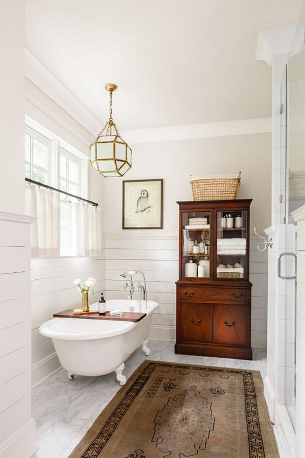 Farmhouse master bathroom with an antique mahogany china cabinet, a beautiful cast-iron claw-foot tub and a Turkish rug.