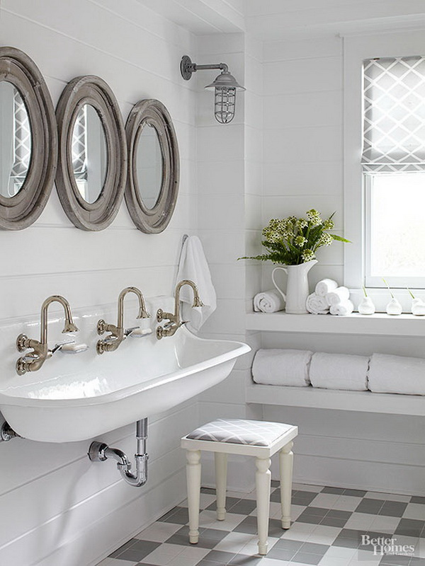 Country-cottage bathroomwith porthole-shape mirrors, caged ship lights, and the wood-clad walls above a farmhouse-style trough sink.