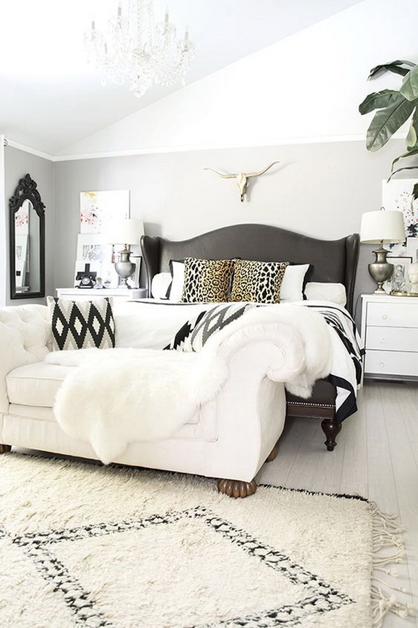 Neutral but bold and beautiful master bedroom with leather studded bed, brass longhorn skull, and black and white accents.