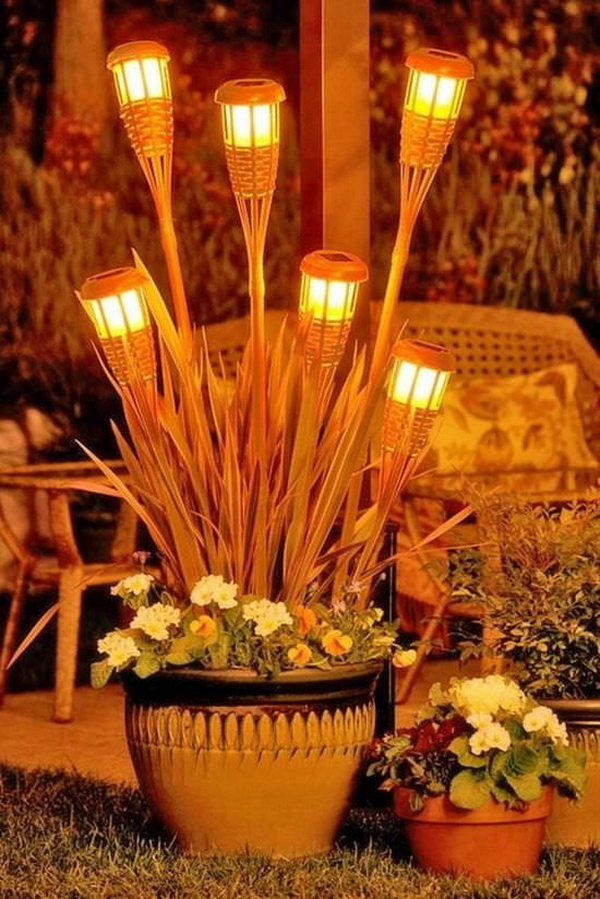 Tiki Torches into Pots. Bunch tiki torches into pots not just sprinkle them around the yard! Super adore this one in my backyard!