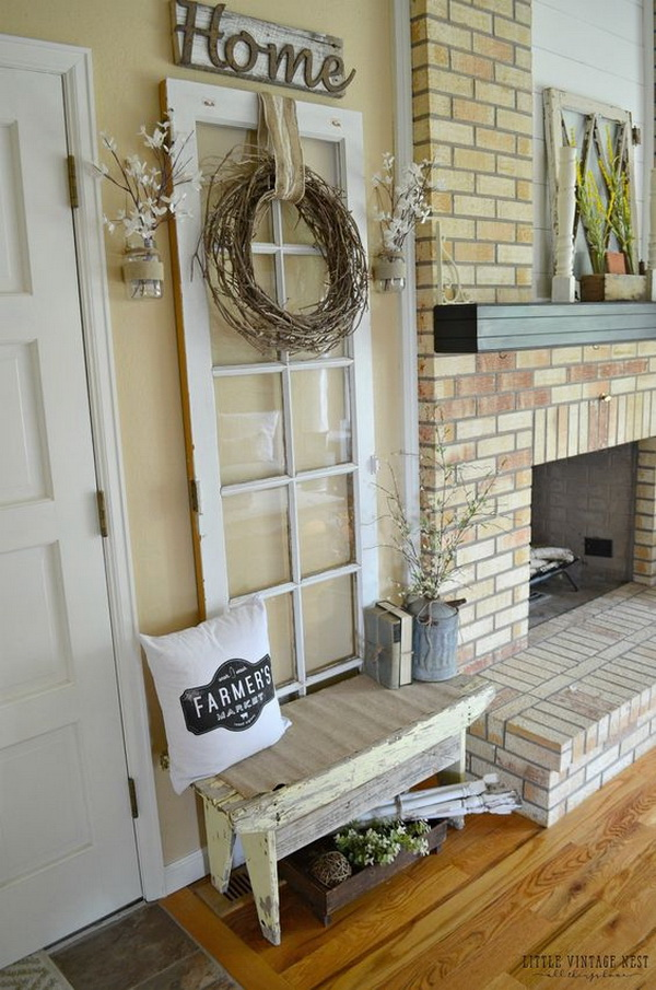 old door leaning against the wall fits in with ease paired with the rustic wooden home sign and the rustic wreath made with branches.