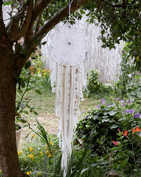 Dreamcatcher DIY. This one has a delicate white lace piece design in the center and drops down with many pieces of fabric scraps. It is a great piece to hang in the bedroom, throughout the home, or in an outdoor space.
