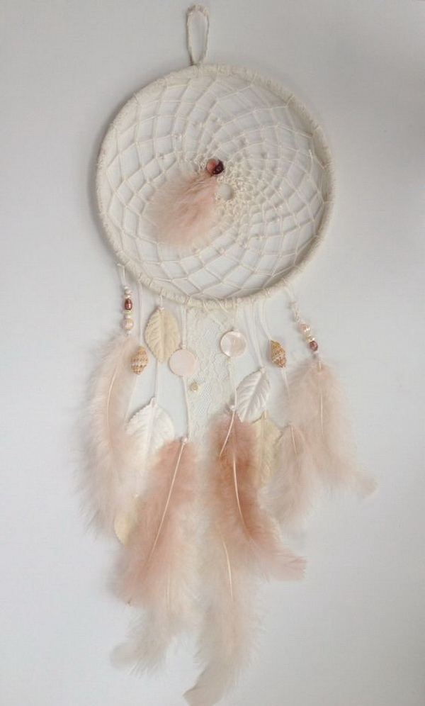 Pink Feathery DIY Dreamcatcher. This pink one looks great in a little girls' nursery or in a cozy reading space. Weaving or crocheting for the hoop, then decorate it with pink and white feathers, beads, seashells and leaves for a vintage-feminine design.