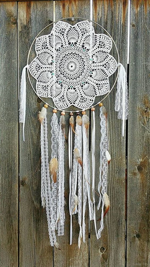 Feminine lacy dream catcher. This dream catcher looks so sleek and elegant with the crocheted floral patterns in the center and the white laces, beads and fluffy white feather hanging down.