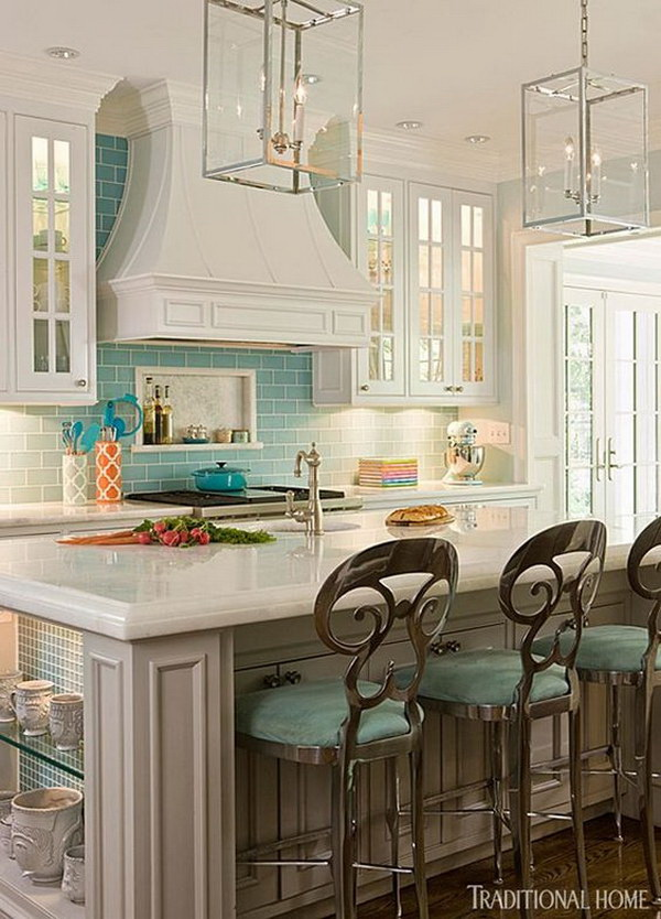 Pale turquoise subway tile backsplash paired with creamy white cabinetry. The turquoise color scheme gives the whole kitchen much more fresh look and feel.