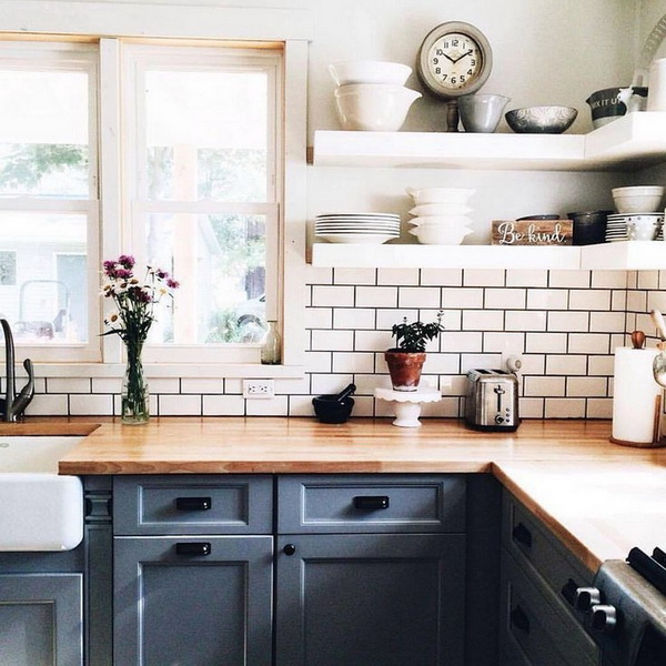 White-tiled walls and backsplash with gray grout give more warmth to this  farmhouse kitchen. The white opening shelvings and the wooden countertops match the backsplash so perfectly.