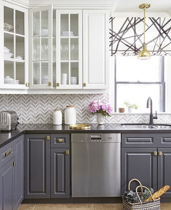 Grey and white chevron tile backsplash with two-tone cabinets.