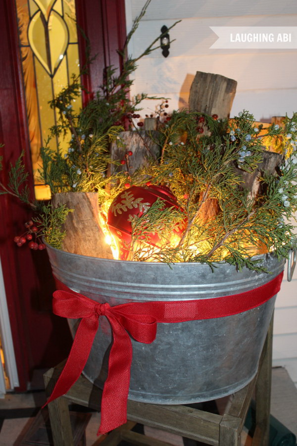 Rustic Christmas Lighted Bucket for Porch Decoration. Fill a summer beer bucket with lots of firewood logs, bright lights and trimmed branches, plus adorned with some oversized ornaments and turn it into a gorgeous piece of decoration for Christmas!