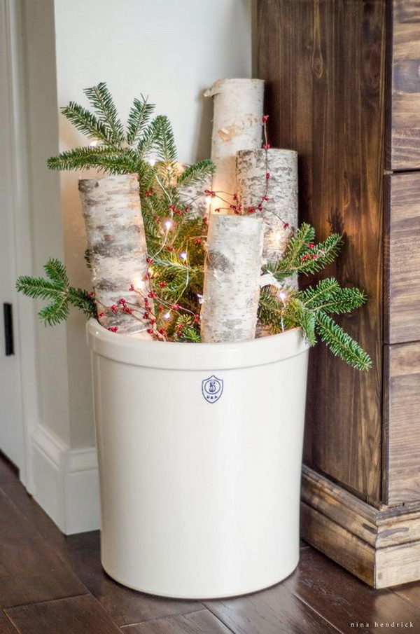 Vintage Stoneware Crock For Outdoor Christmas Decor. Small decor makes a whole difference for farmhouse decor like this is tiny, easy to create centerpiece. Love the stoneware crock with arrnagement of trunks, pine branches, berries and a string of lights.