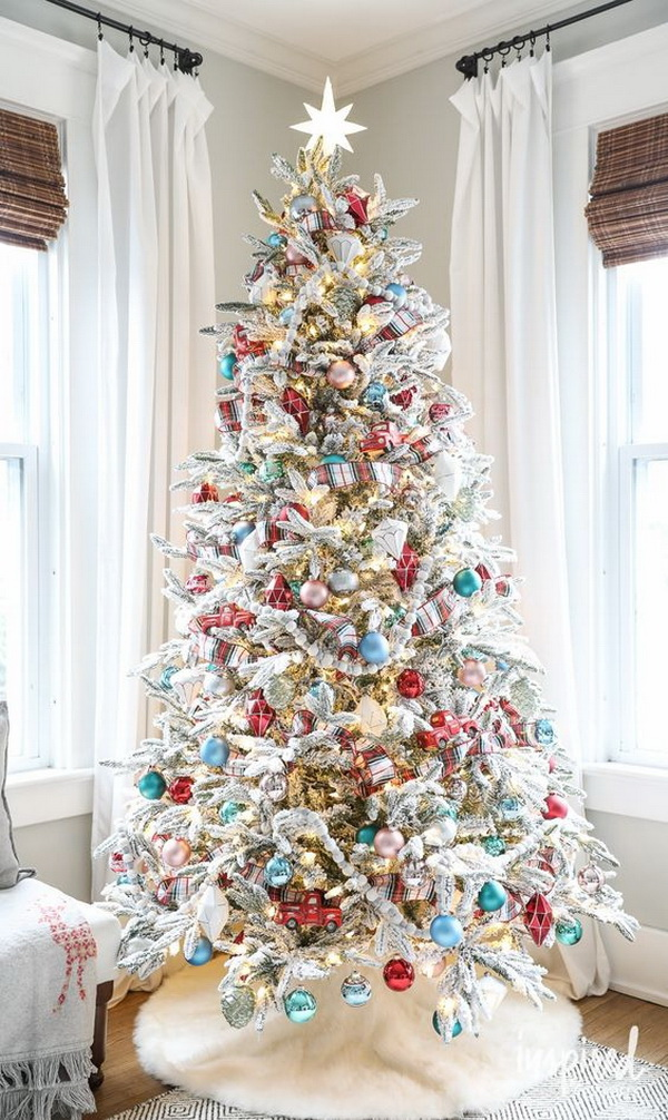 Winter wonderland Christmas tree. Love the frosted look paired with a pop of colors! Love the color scheme of the red and blue ornaments!