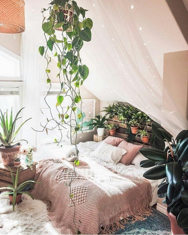 Romantic bohemian bedroom with canopy and lots of plants inside.