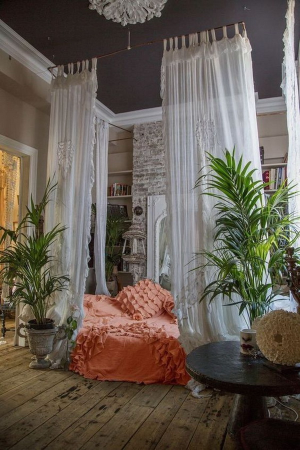 Bohemian style bedroom with crutains arround the bed.