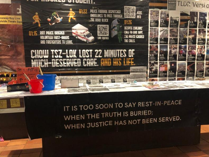 "a memorial with a banner reading ""it is too soon to say rest in peace when the truth is buried. when justice has not been served."" above is a sign reading ""chow tsz-lok lost 22 minutes of much-deserved care. and his life."""