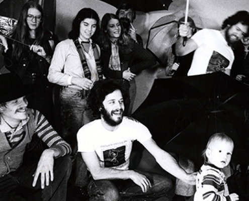 The 1979 crew from Forecast gather for a photo with umbrellas as props (black and white)