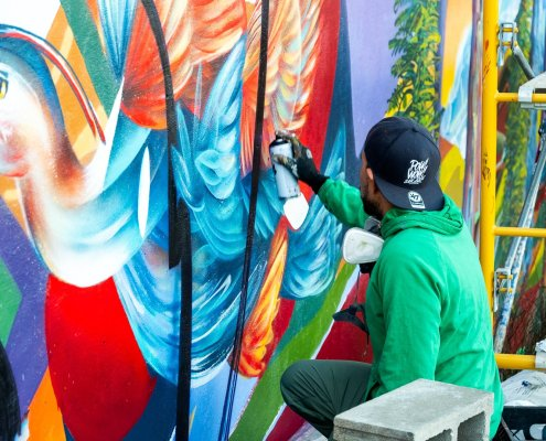 Artist Yatika Fields spray paints a colorful wall