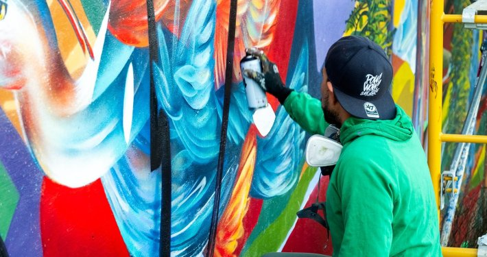 Artist Yatika Fields spray paints a colorful wall