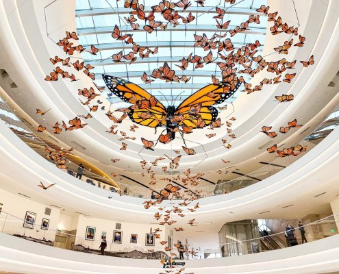 A 30-foot Monarch butterfly installed in a mall atrium, surrounded by hundreds of smaller butterflies
