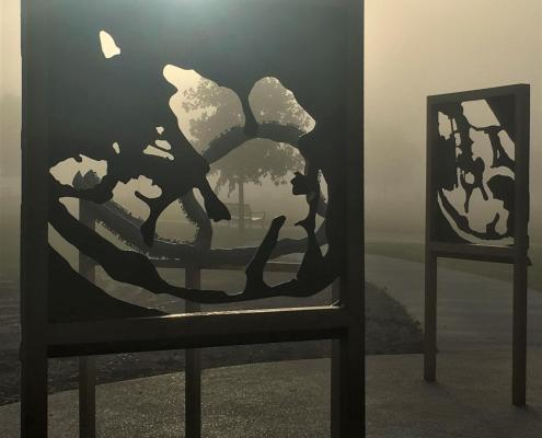 misty sunshine pours through the negative relief space carved into two standing metal sculpture plaques that depict the shape of the nearby lake