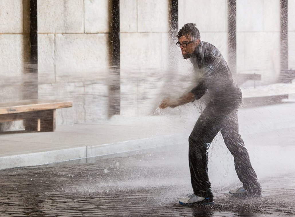 the artist Dread Scott leans into a stream of water that's shooting at him from a fire hose