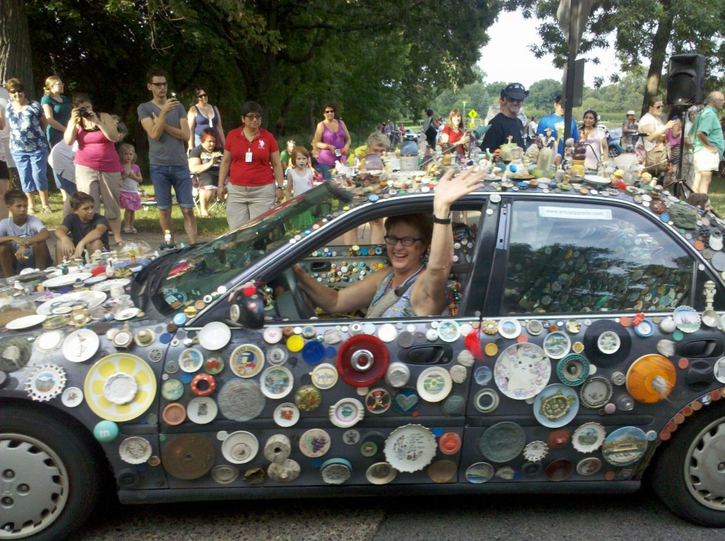 a woman driving a art-bedazzled car waves to an onlooking crowd