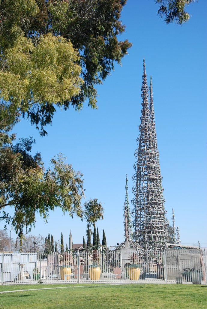 a metal spire tower stands out among smaller structures behind a tree