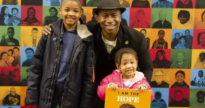 "The mayor of Brooklyn Center poses with two children in front of community banner. The younger child, around 3 to 4 years old, holds a banner featuring their face and the word ""hope."""